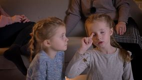 Close-up portrait of small caucasian girls watching movie attentively and talking with each other in cosy home stock footage