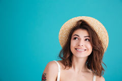 Close up portrait of a smiley young girl in straw hat. Looking away at copyspace  over blue background Royalty Free Stock Photo
