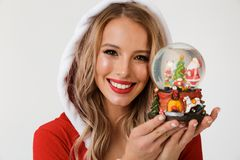 Close up portrait of a smiling blonde woman. Dressed in red New Year costume standing over white background, holding snowball stock images