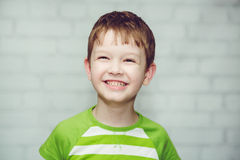 Close-up portrait of a smiling boy on a light background. Royalty Free Stock Photo
