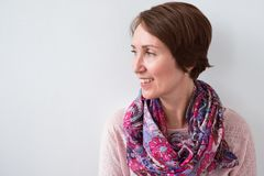 Close up portrait of smiling brunette woman with colorful scarf. She looks aside curiously Royalty Free Stock Photo
