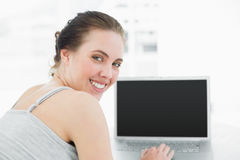 Close up portrait of a smiling casual woman with laptop. Close up portrait of a smiling casual young woman with laptop at home Stock Photography