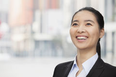 Close-up portrait of smiling, confident, young businesswoman with a ponytail looking up, outdoors with skyscrapers in the backgrou Royalty Free Stock Photography