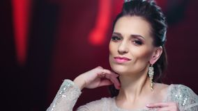 Close-up portrait smiling fashion woman with evening makeup posing at red lights studio background stock video footage