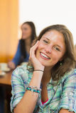 Close up portrait of a smiling female at  coffee shop. Close up portrait of a smiling female with students in background at  the coffee shop Stock Images