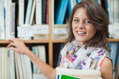 Close up portrait of a smiling female student against bookshelf in the library Royalty Free Stock Photography