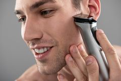 Joyful young man shaving with electric razor. Close up portrait of smiling gentleman removing stubble from cheek with shaving machine.  on blue-gray background royalty free stock photos