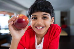 Close-up portrait of smiling girl with fresh apple. At home Royalty Free Stock Images
