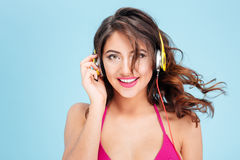 Close-up portrait of smiling girl listening music with earphones Stock Photos