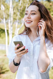 Close-up portrait of a smiling girl listening to music. Close-up portrait of a smiling young girl listening to music with earphones outdoors Stock Photos