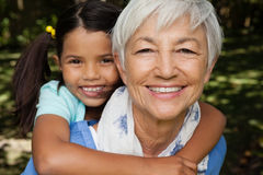 Close-up portrait of smiling grandmother giving piggyback to granddaughter. At backyard Stock Photography