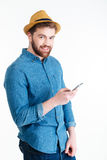 Close-up portrait of smiling handsome man texting using smartphone Royalty Free Stock Image