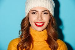 Close up portrait of smiling happy girl in winter hat. Looking at camera  over blue background Royalty Free Stock Photo