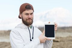 Close-up portrait of a smiling hipster in a brown cap outdoor holding a white tablet computer with a cut-out blank for royalty free stock images