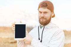 Close-up portrait of a smiling hipster in a brown cap outdoor holding a white tablet computer with a cut-out blank for stock photo