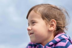 Close-up portrait of a smiling little girl's profile Stock Image