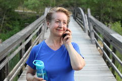 Close-up portrait of a smiling mature woman using mobile phone in the forest while crossing a wooden bridge Royalty Free Stock Photography