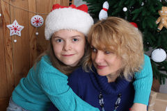 Close up portrait. Smiling mother and daughter with Christmas decorations Royalty Free Stock Photography