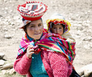 Close up portrait of a smiling Quechua woman dressed in colorful traditional handmade outfit and carrying her baby in a sling Stock Image