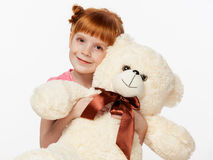 Close up portrait of a smiling red-haired girl with a bear toy Royalty Free Stock Image