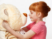 Close up portrait of a smiling red-haired girl with a bear toy Royalty Free Stock Photography
