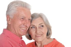 Close-up portrait of smiling senior couple wearing bright clothing. Smiling senior couple wearing bright clothing isolated on white background stock photography