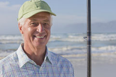 Close up portrait of smiling senior man with fishing rod on sunny beach Royalty Free Stock Photo