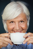 Close up portrait of smiling senior woman with coffee cup Royalty Free Stock Images