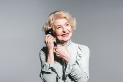 Close-up portrait of smiling senior woman talking by vintage phone. Isolated on grey stock image