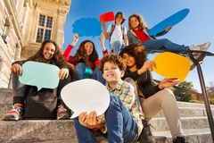 Smiling teenage boys and girls with speech bubbles. Close-up portrait of smiling teenage boys and girls sitting on the stairs outdoors, holding colorful blanked Royalty Free Stock Photography