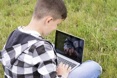 Cheerful teenager chatting on modern laptop royalty free stock photo