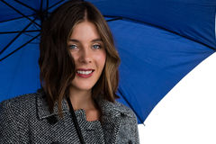 Close up portrait of smiling woman with blue umbrella. Against white background Royalty Free Stock Image