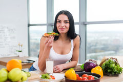 Close-up portrait of smiling woman eating diet vegetarian sandwich with vegetables for breakfast in morning, looking at Royalty Free Stock Photography