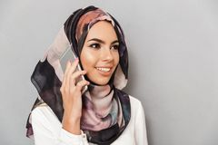 Close up portrait of a smiling young arabian woman. Close up portrait of a pretty young arabian woman talking on mobile phone isolated over gray background Stock Image