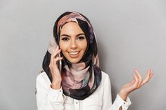 Close up portrait of a smiling young arabian woman. Talking on mobile phone isolated over gray background Stock Photo