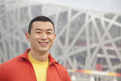 Close up portrait of smiling young athletic man in park, looking at camera, with modern building in the background in Beijing, Chi Royalty Free Stock Photos