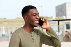 Close up of smiling young black man talking on cellphone outdoors. Close up portrait of smiling young black man talking on cellphone outdoors stock images