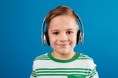 Close-up portrait of smiling young boy listening music by earphone Stock Photos