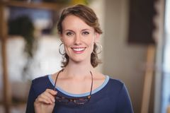 Close up portrait of smiling young waitress holding eyeglasses. At coffee shop Royalty Free Stock Image