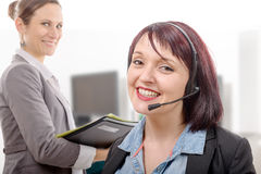 Close-up portrait of smiling young woman with headset Stock Image