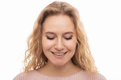 Close up portrait of a  smiling young woman  wearing a pink dress .with closed eyes on white background.  Dreamer. Close up portrait of a positive smiling young royalty free stock photo