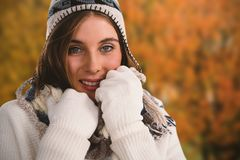 Composite image of close up portrait of smiling young woman in sweater. Close up portrait of smiling young women in sweater against tree growing outdoors Stock Images