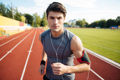 Close up portrait of a sports man running with earphones Royalty Free Stock Image