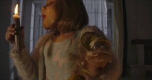 Close-up portrait of strange Caucasian girl blowing out candle and holding doll in other hand. Weird child alone at