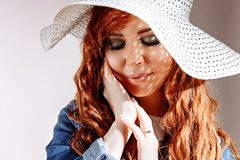 Redhead woman wearing hat on white background royalty free stock images