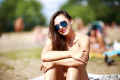 Close up portrait of stylish beautiful sexy woman in glasses and with wet hair on a sunny beach with blue water.  Royalty Free Stock Photo