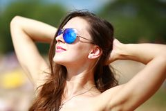 Close up portrait of stylish beautiful sexy woman in glasses and with wet hair on a sunny beach with blue water. Sunbathe and enjoy the rest Royalty Free Stock Photography