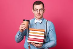 Close up portrait of stylish hard working young guy looks directly at camera, holds many books in one hand, drinking coffee from royalty free stock images