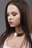 Close-up portrait. Stylish makeup, gold necklace, beautiful btunette model looking down Royalty Free Stock Images