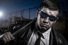 Close up portrait of stylish secret dangerous man with steel baton. Close up portrait of suspicious, dangerous looking brutal man, wearing leather coat and black Stock Image